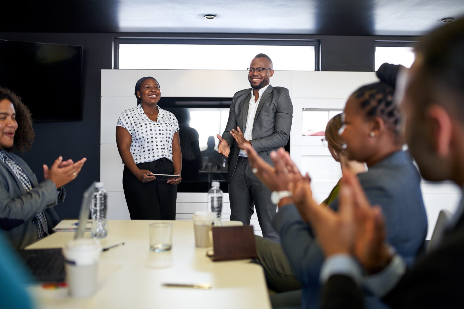 Attractive black businessman being encouraged by diverse multi-ethnic group of coworkers during presentation in office